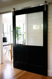 this industrial barn door has a huge glass panel to allow natural light while still closing off the room