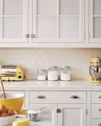 white and yellow kitchens with creamy white shaker kitchen cabinets paired with marble countertops and off white subway tile backsplash