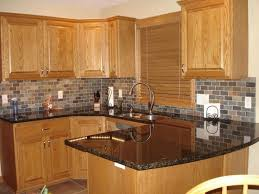 honey oak kitchen cabinets with black countertops matching countertops with backsplash
