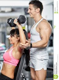 gym instructor fitness trainer helping girl in a gym stock photo image of