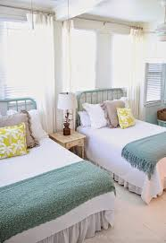 View in gallery Bright and beach-themed twin beds in a guest room