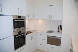 white wooden kitchen cabinet with steel sink on white kitchen wall