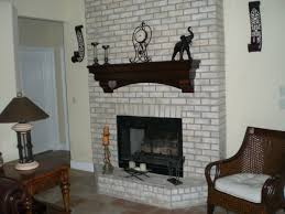 interior white brick fireplace with black mental fire box and black wooden mantel shelf o