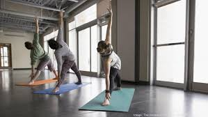 men and woman practicing yoga triangle pose in yoga cl studio