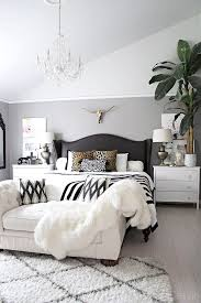 attractive black and white headboard neutral bedroom with crystal chandelier on tufted chaise black