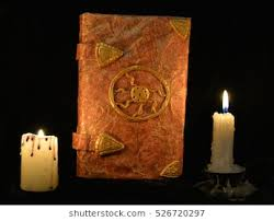 old book of fairy tales with burning candles in the darkness concept black