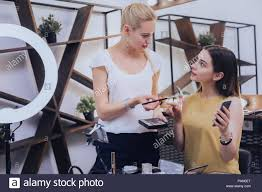 dark haired young woman having consultation with makeup artist