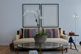 centerpiece for round glass coffee table featuring single big white orchid on natural vase filled green