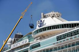 a crane loads cargo on the royal caribbean s liberty of the seas cruise ship as it