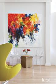 In the living room, white walls showcase a vibrant oil painting, Forgetful  Summer Paints