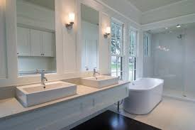 double sink vanity with bathroom mirror and wall sconces for bathroom makeover also freestanding tub with windows and glass shower enclosure plus