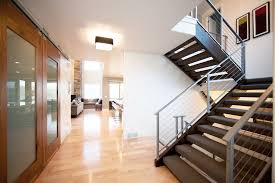 Contemporary Staircase with High ceiling, flush light, Hardwood floors