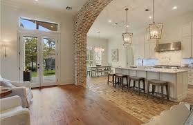 Wood floor room Laundry Open Floorplan With Wide Arch Pillars Tile Transitions San Diego Marble Tile