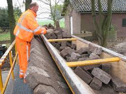 A worker transferring bricks from the hopper to the pusher
