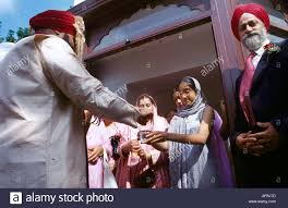 sikh wedding brides sister offering gift to groom at entrance of gurdwara shepherds bush london england
