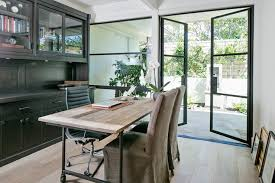 home office boasts glass front cabinets over black built in cabinets with under cabinet lighting a black paneled backsplash facing a wood and iron desk