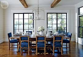this beautiful and elegant white wood panelled dining room has rustic faux beams across the