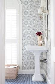 breathtaking powder room boasts walls clad in white and blue wallpaper zoffany spark wallpaper lined with a frameless mirror illumi bathroom ideas in