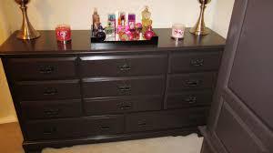 black bedroom vanity with drawers beside black wood cupboard