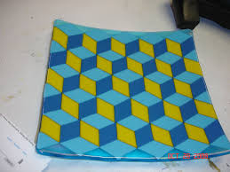 this is a fused glass plate with a geometric pattern that really looks 3 d makes me want to walk up the stairs