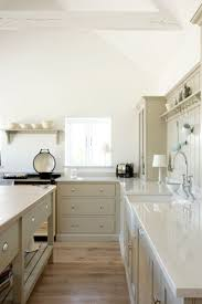 kitchen colors images: elegant cream kitchen features cream cabinets adorned with aged brass cabinet pulls alongside gray perimeter counters which frame an aga range below a cream