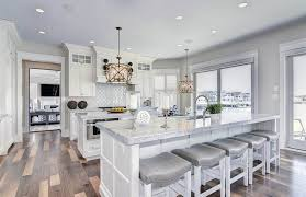 transitional kitchen with double islands white cabinets light gray paint and walnut hardwood flooring
