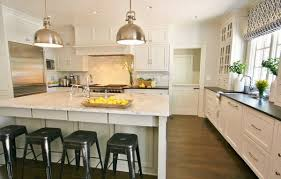 white kitchen cabinets black countertop wood flooring honed