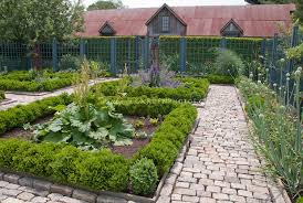 upscale vegetable garden with cut stone walkway fence trellised apple fruit trees and beautiful