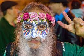 bearded man painted mask flowers crown