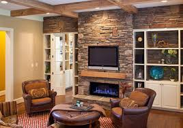 interior tall stone fireplace with black tv on over brown wooden fireplace mantels plus white