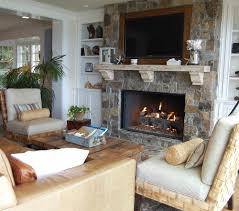 armchairs with wood coffee table and decorative pillows also fireplace mantel plus leather couch and palm trees also stone fireplaces for beach style living