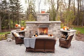 outdoor fireplace design with concrete stony mantel and wood storage and three rattan sofa