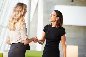 reasons to befriend the practice of informational interviewing two businesswomen shaking hands in modern office