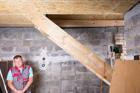 Design Builder Wearing Vest Standing In Unfinished Basement Underneath Wooden Stairs And Looking Down Towards Floor Inside New Home Construction Site Photo By Depositphotos Builder In Unfinished Basement Looking Down Stock Photo