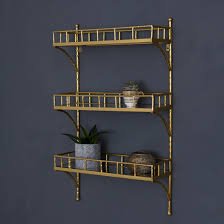 gold metal bamboo framed wall storage unit with three shelveirrored surface