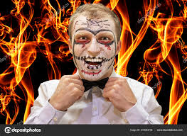 joker makeup on face of man on burning flame fire background scary devil man