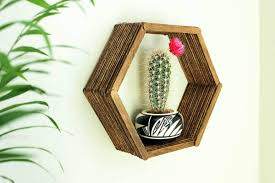 a hexagon shaped shelf made out of popsicle sticks is hanging on the wall holding a