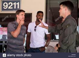 """Brian Dietzen and Duane Henry, leading cast members of the CBS hit drama  """"NCIS: Naval Criminal Investigations,"""" listen to a Marine explain the  capabilities of an CH-53E Super Stallion during a USO"""