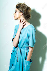 attractive fashionable woman with bright makeup and chignon in light blue dress standing on white background