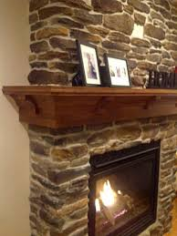 interior ture of interior fireplace design using solid oak wood shelf over fireplace along with custom made fireplace mantels and natural stone