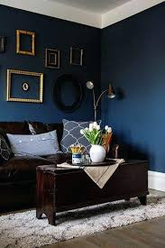 this living room smartly balances its dark blue walls and brown couch with white tulips gold dark living room floor ideas