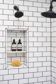 shower with white subway tiles and black grout