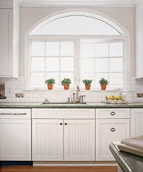 touches of beadboard on the cabinets mixed in with flat panel door and drawer fronts give this light filled kitchen personality and old fashioned charm