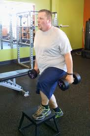 dennis lyons does a step up exercise carrying two dumbbell weights during his thursday workout at anytime fitness