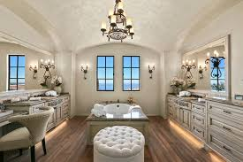 traditional master bathroom with chandelier wall sconces drop in tub and hardwood flooring