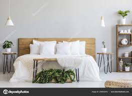 lamps wooden bed white sheets grey bedroom interior pouf plants stock photo