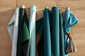 rolls of teal sunbrella upholstery fabrics against outside wall