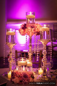 Perfect example of a low table decor for less. Small floral cuffs atop  silver candle sticks with hanging swarvoski crystal defiantly warms up the  mood.