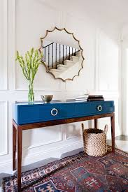 modern entry with midcentury style table in blue lacquer finish