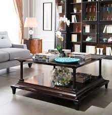 books and tiny glass vase with white orchid centerpiece for two tiers coffee table interesting